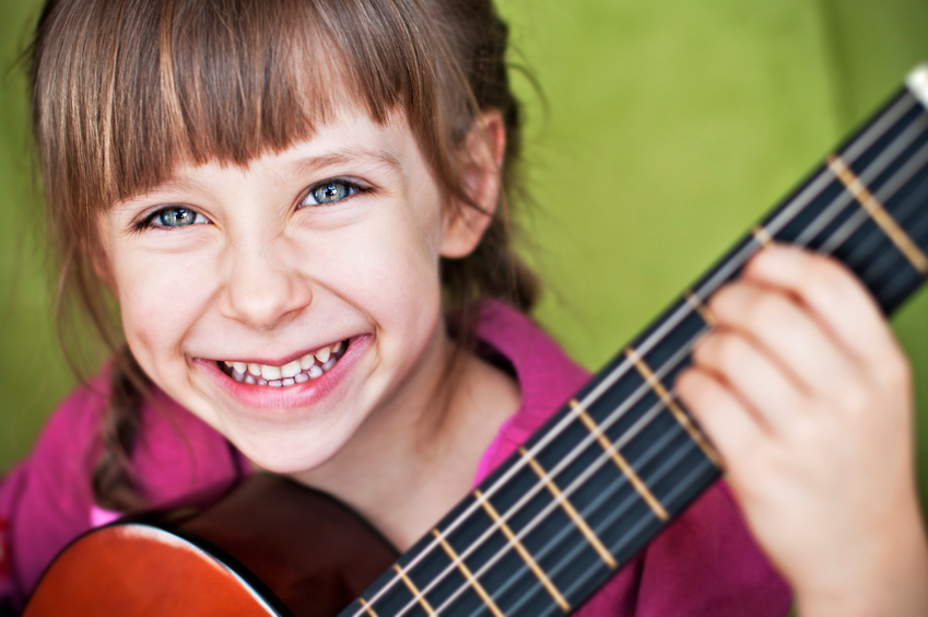 Closeup of little girl playing a guitar. Fine noise applied. Slightly soft focus. Very shallow depth of field.